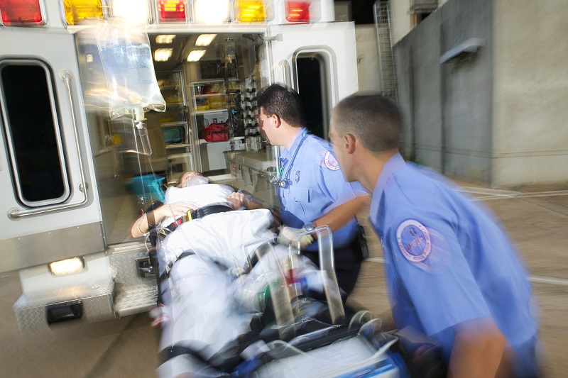 Two EMT persons transporting a person in a stretcher into an ambulance