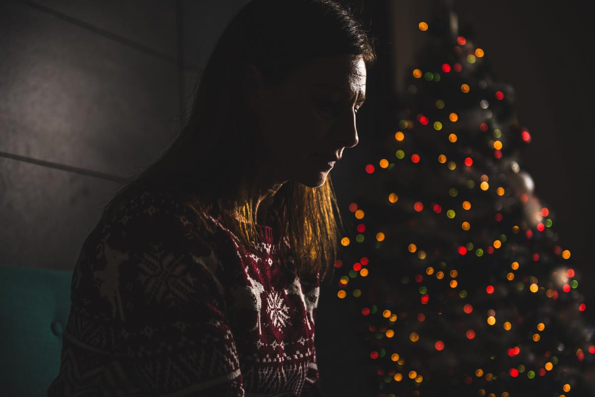 Sad woman by Christmas tree