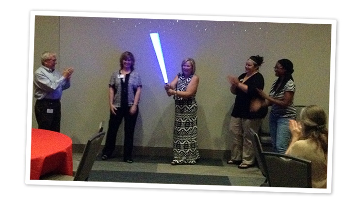 A photo from a Star Wars themed video and movie event. A group of people applaud as one woman holds a light saber