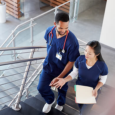 Two nurses walking up the stairs.