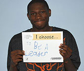 picture of a young man holding a sign that reads I choose to be a leader
