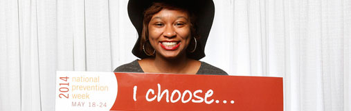 A young African American woman holding an I Choose poster