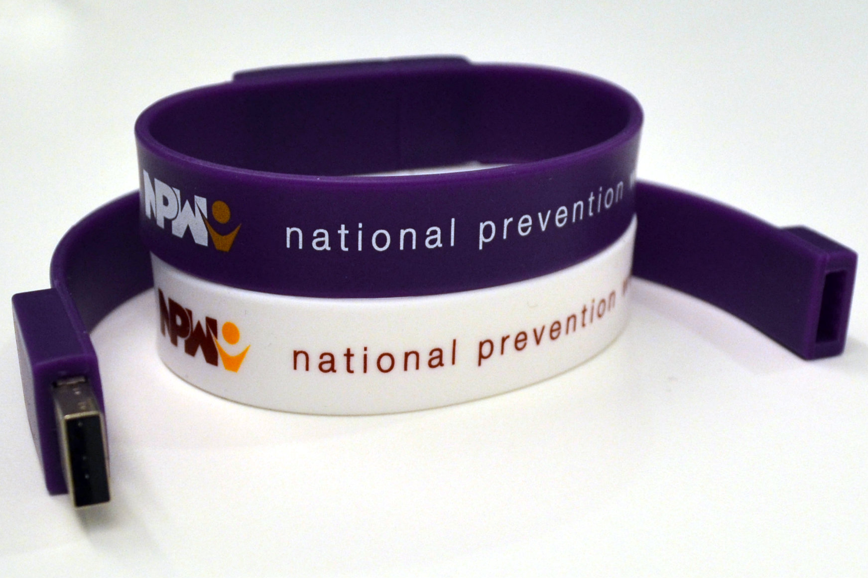 one purple and one white NPW USB wristbands