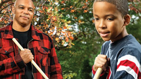 father and son raking leaves together